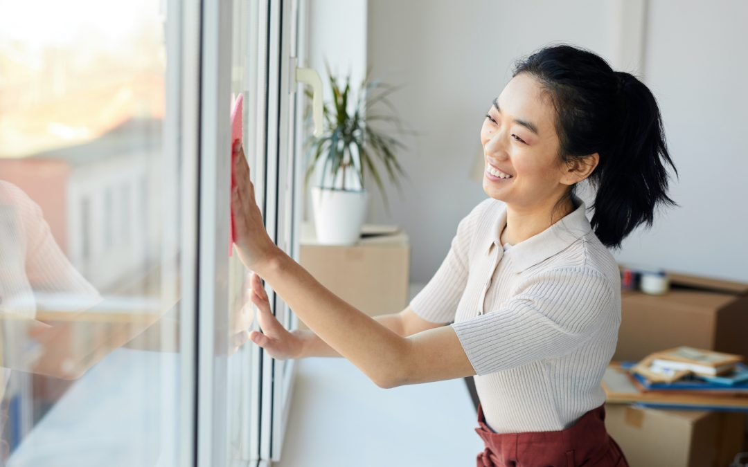 Young Asian lady cleaning the inside of the windows in her home.